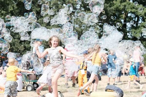 young girl happy and running through a big bubble
